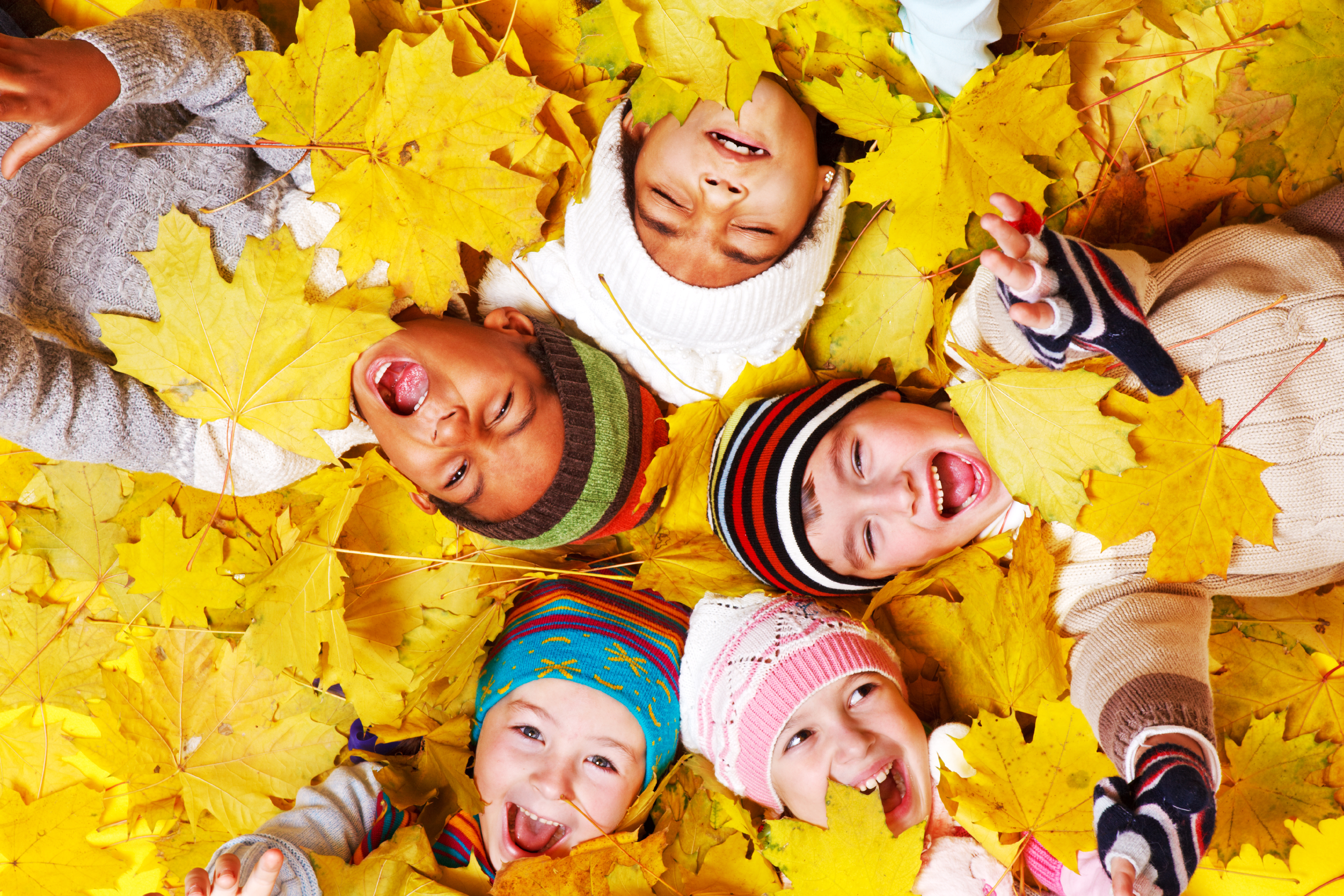 Kids having fun in a pile of leaves. Omaha Dentistry post on autumn safety for dental health.