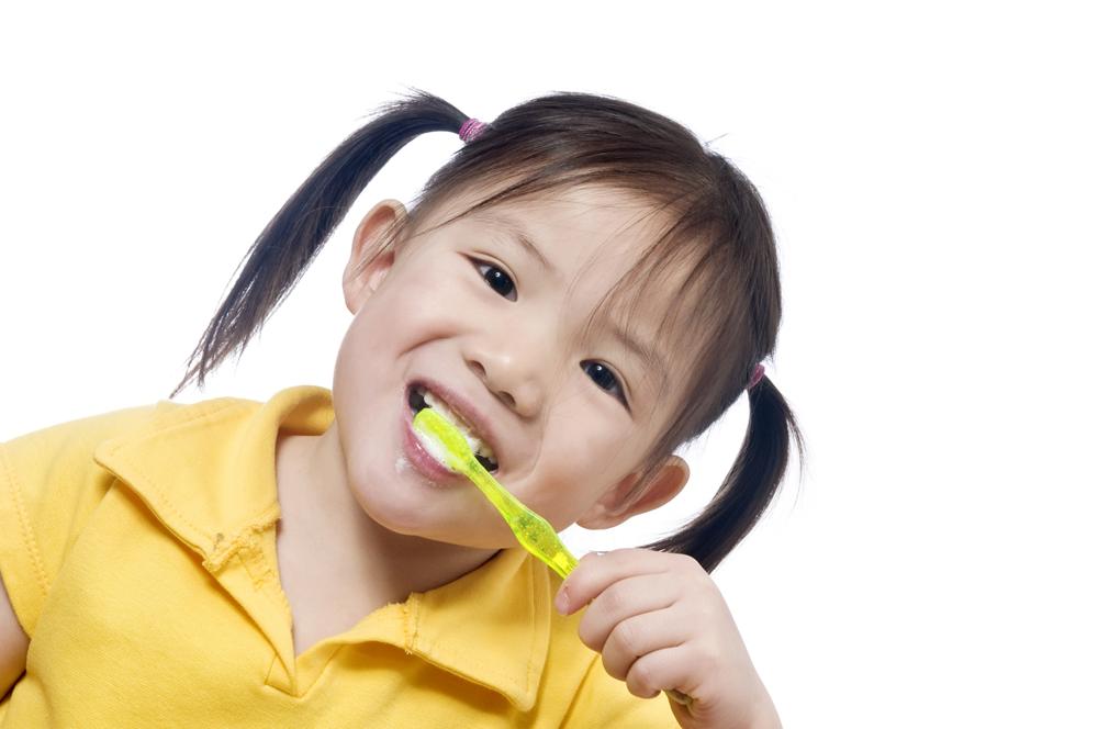 Girl in pigtails brushing her teeth | Omaha dentistry