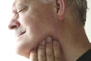 Omaha TMJ dentist, TJ Bolamperti. Man suffering from TMJ syndrom