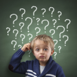 little boy with puzzled look on his face in front a green chalkboard with question marks. FAQ small