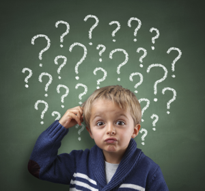 Small boy with puzzled look standing in front of a green board with questions marks | AQ for Omaha Dentistry