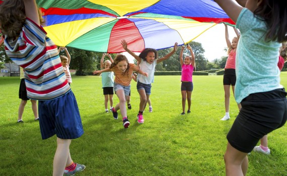 Kids lifting multi-colored parachute and running under it
