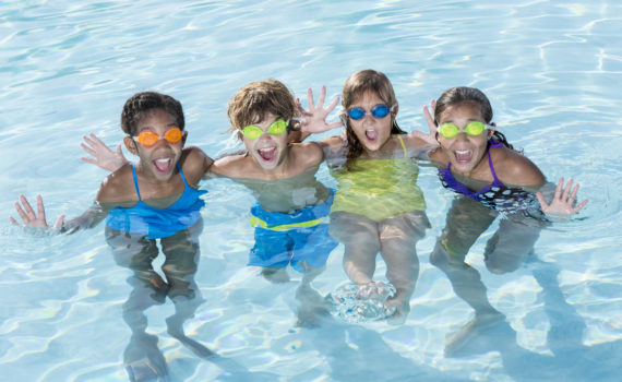 Multi-ethnic group of children having fun in swimming pool. Ages 9 to 13.| Omaha Dentistry Dental Safety for summer