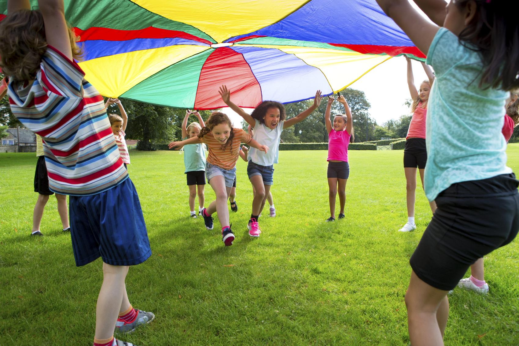 Children running under a colorful tarp | Summer Dental Health | Omaha Dentistry